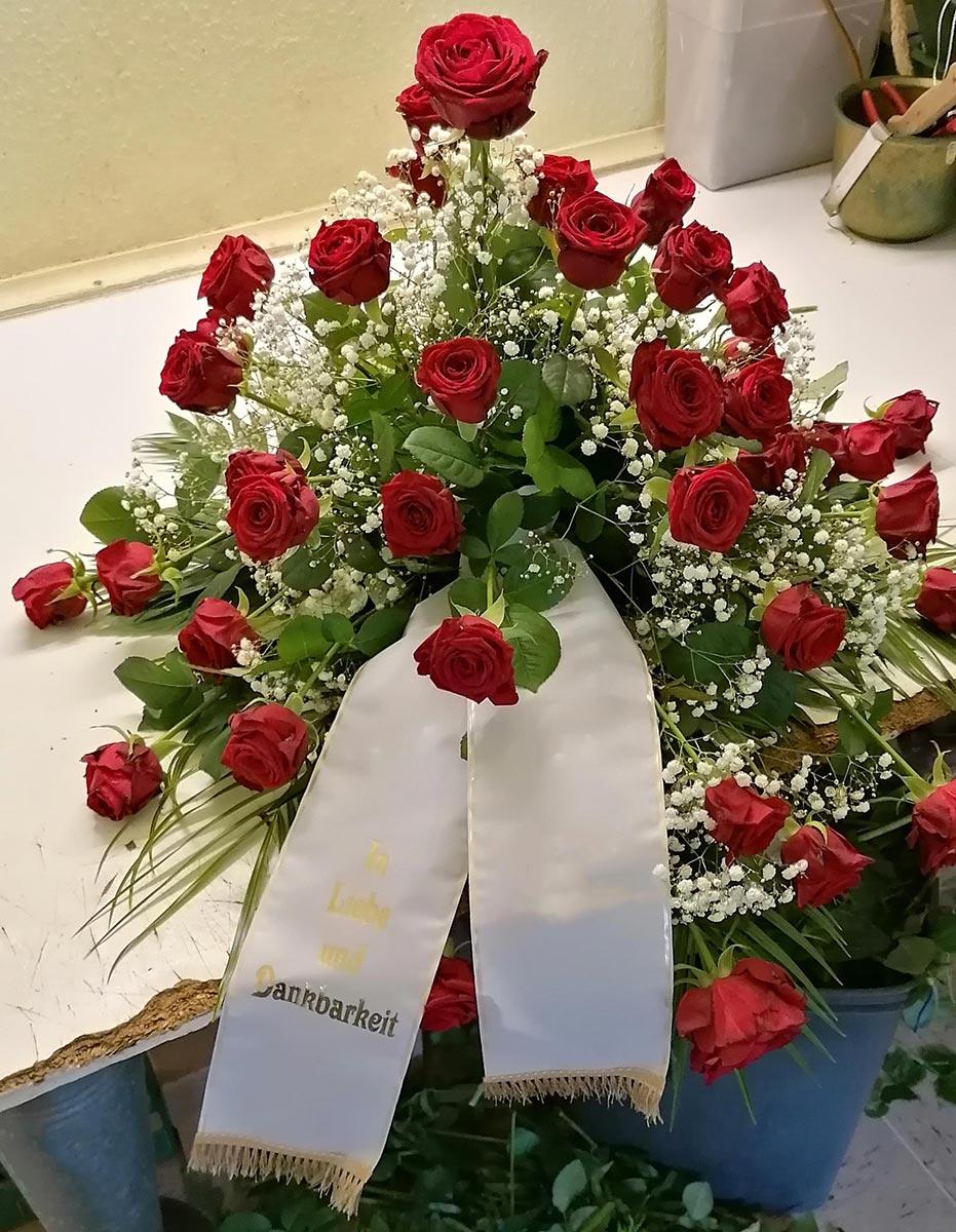 Grab Gesteck rote Rosen Schleierkraut